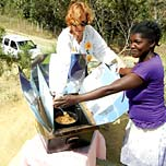 Two women using a solar cooker