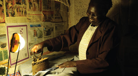Kenyan woman ironing clothes by the light from a solar lantern