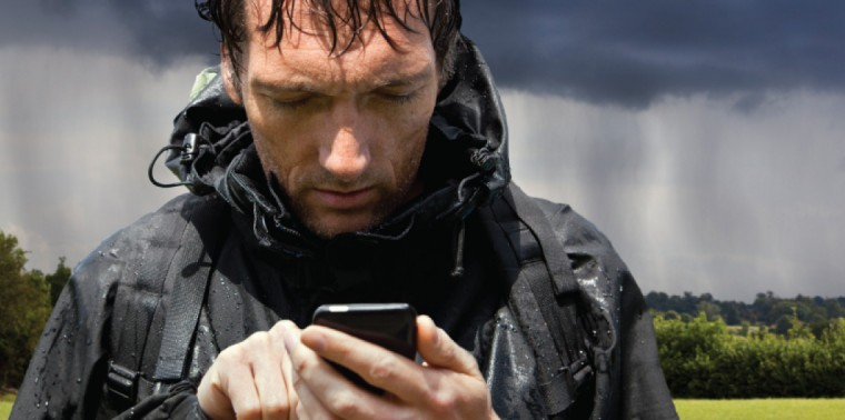 Rain soaked hiker using smartphone