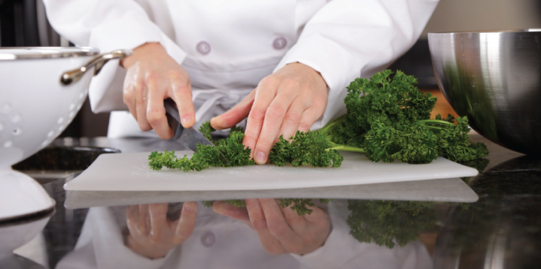 A close-up of a chef's hands cutting vegetables