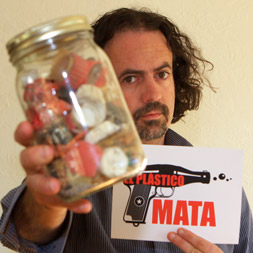 Manuel Maqueda holds a jar containing the stomach contents of a single baby albatross found dead on Midway island. Photo by ElPlasticoMata.com