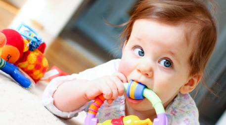 Baby chewing on plastic toy