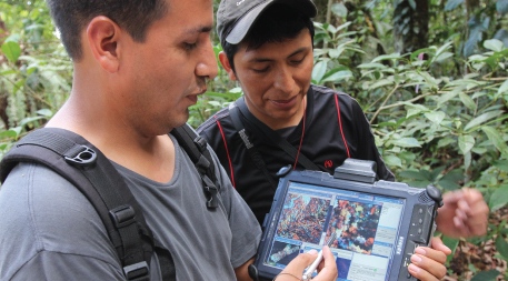 Two men in the Amazon with data on screen