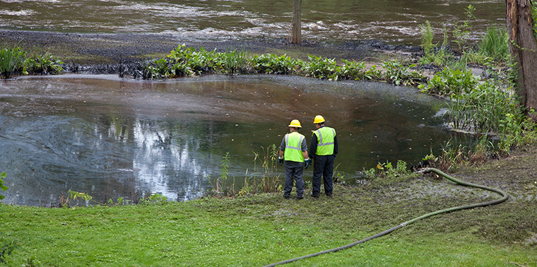 Two workers cleaning up after oil spill