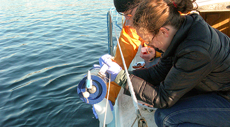 """Ryan Kelly and graduate student Natalie Lowell take a sample in Seattle as part of a project comparing the eDNA """"signatures"""" of freshwater and saltwater. Photo by Kathryn Graziano."""