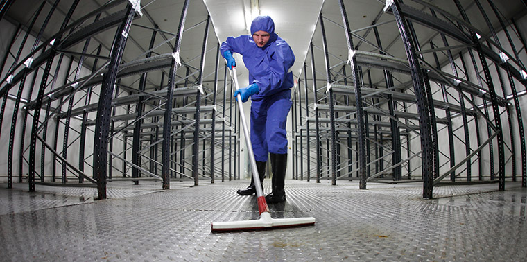Worker in protective uniform cleaning a floor in an empty warehouse