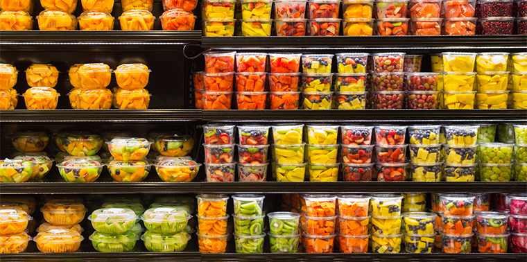 Assortment of cut fruit in plastic containers on display for sale at the supermarket