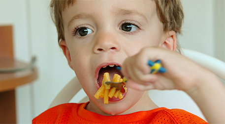 Child eating macaroni