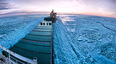 Icebreaker towing cargo ship through thick ice-field in Finland.
