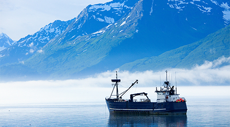 Large fishing boat anchored in Valdez, Alaska bay. Chugach Mountains in background.