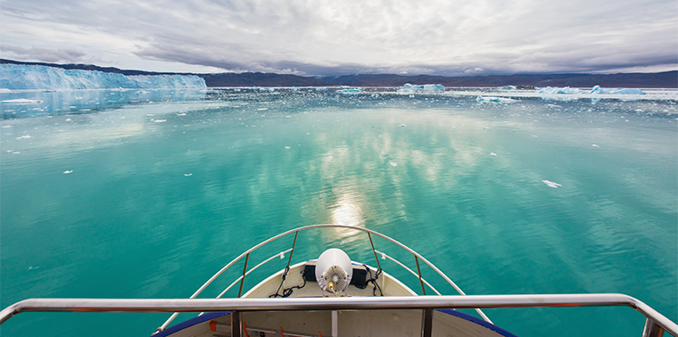 Panoramic view over boat bow towards the tranquil turquoise artic waters at the Eqi Sermia Glacier and Greenland Coast. Eqi Glacier, Ilulisaat, North West Greenland.