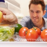 Man looking at produce in refrigerator