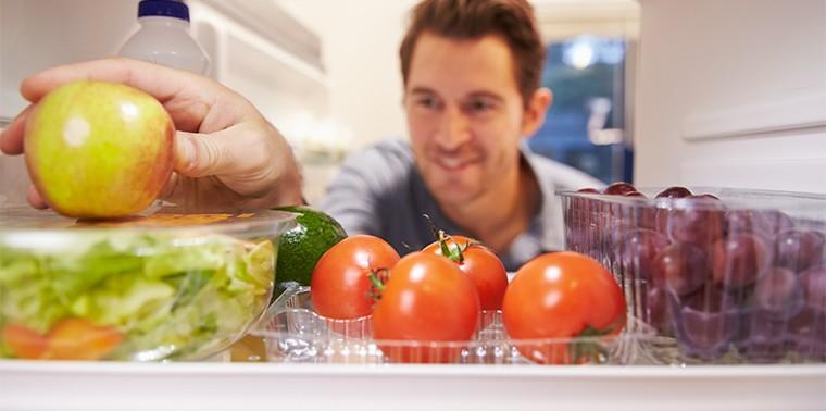 Man looking at produce in refrigerator