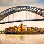 Cargo ship passing under bridge