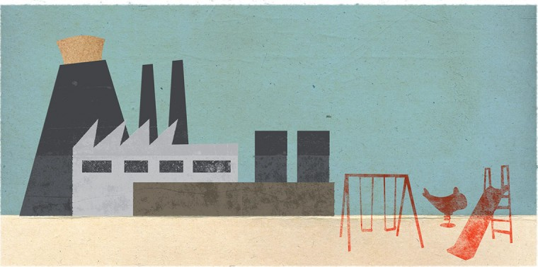 Factory with cork in smokestack next to playground