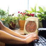 Woman using space heater at her desk in summer