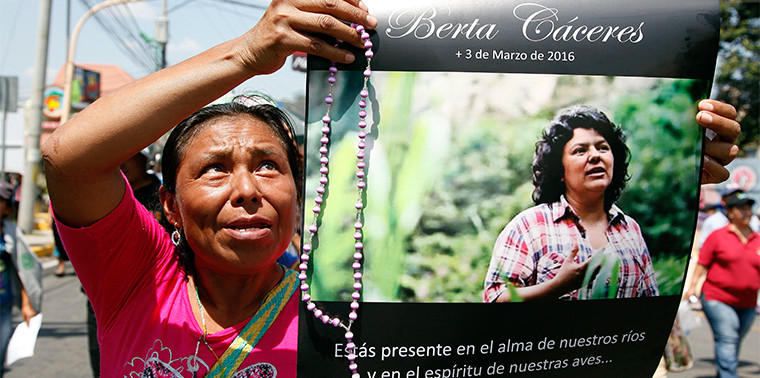 Woman holds up a poster with a photo of slain environmental leader Berta Caceres