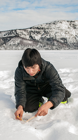 Charles Oudzi, of Colville Lake, collects caribou fecal pellets