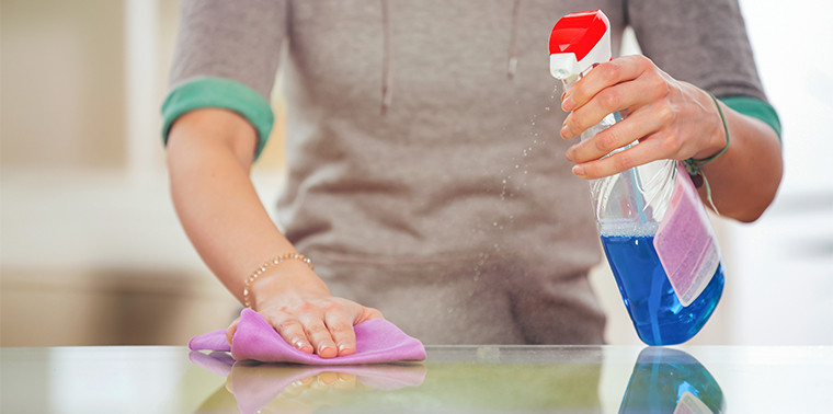 Woman cleaning glass table with spray