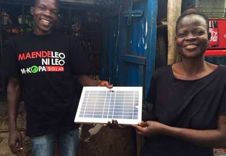 Consonlata Andhiambo Odero, who lives in western Kenya and is seen here with an M-KOPA sales rep, is all smiles as she shows off new M-KOPA solar panels that are powering solar-powered lamps so her kids can read at night. Photo by Peyton Fleming