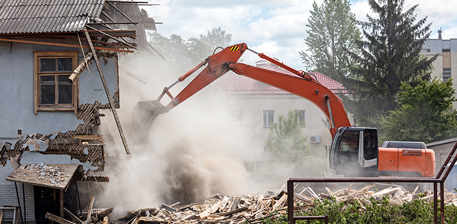 Although deconstruction can offer benefits such as less waste and more jobs, it also costs more and takes longer, meaning demolition is still the mainstream option. Backhoe demolishing a house.