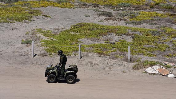 Border Patrol agent rides an ATV through Tijuana River National Estuarine Research Reserve