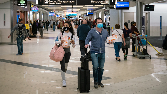 travelers at airport wearing face masks to prevent disease transmission
