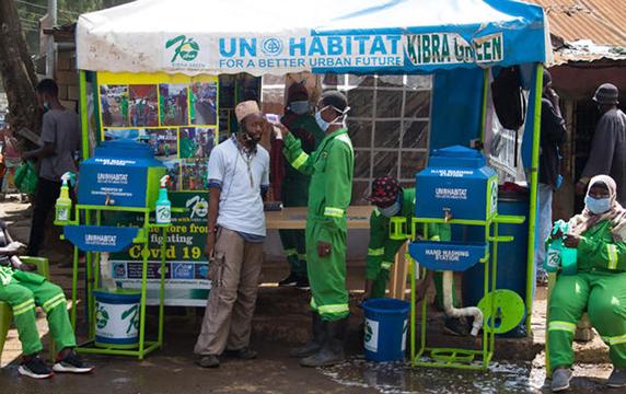 UN-Habitat and Kibra Green partner to address Covid-19; medical professional takes man's temperature