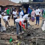 People pick up trash in Kibera