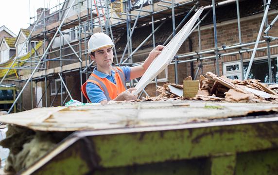 construction worker putting construction debris in trash