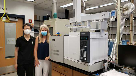 Susan Richardson (right) and graduate student Jiafu Li stand next to a machine that allows them to quantify trace levels of DBPs in drinking water, and identify new ones at the same time.