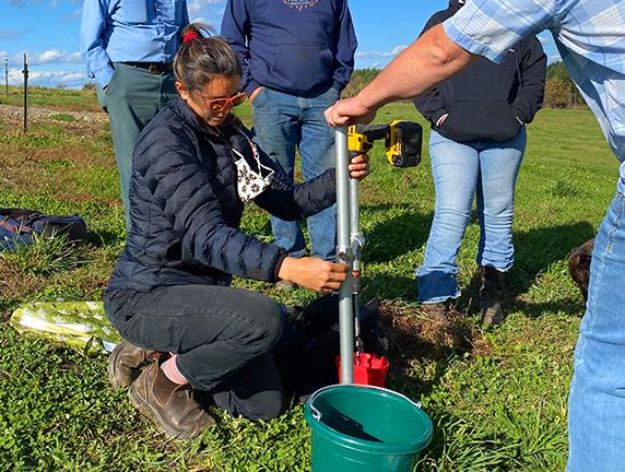 Leah Puro and Jason Johnson take a soil sample
