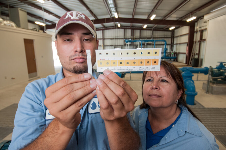 Freer Water Control and Improvement District Manager Diana Adame, right, and plant worker Anthony Arredondo, compare a test strip to a calibration chart to show water from Freer, Texas has less than one part per billon of arsenic